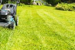 Кося лужайки, травокосилка на зеленой траве, оборудовании травы косилки, кося инструменте работы заботы садовника, конце вверх по Стоковая Фотография