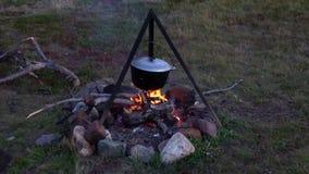 Котел нагрет на огне Варить еду в экспедиции видеоматериал