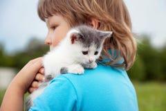 Котенок на руке мальчика outdoors, ребенок огромный его любимчик влюбленности Стоковое Изображение RF