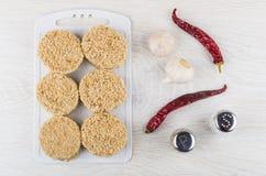 Котлеты сырого мяса на разделочной доске, чесноке, перце chili, соли Стоковое Изображение RF