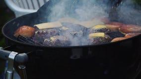 Котлеты чизбургеров на барбекю зажаренном верхней частью внешнем сток-видео