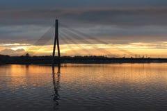 , который кабел-остали мост через реку западной Двины в Риге во время захода солнца Стоковые Фото