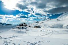 Коттедж зимы высокий в горах Стоковое Фото