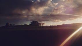 Коттедж и заход солнца во время отключения дома назад стоковая фотография