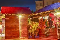 Коттедж продавца одежд зимы с освещениями рождества вокруг на главной площади делает Стоковые Фото