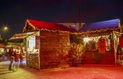 Коттедж продавца одежд зимы с освещениями рождества вокруг на главной площади делает Стоковое Изображение