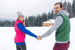 Коттедж курорта снега зимы человека и женщины загородного дома молодой деревни Snowy пар деревянный Стоковые Изображения RF