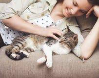 Кот молодой женщины прижимаясь дома Стоковые Изображения RF