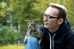Кот сидит на подоле человека Стоковая Фотография RF