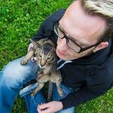 Кот сидит на подоле человека Стоковые Изображения