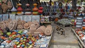 Кот среди пестротканых товаров на африканском рынке Стоковая Фотография
