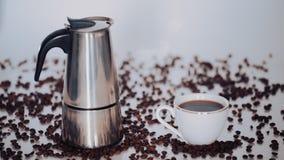 Кофеварка гейзера, кофейная чашка и кофейные зерна на белой предпосылке сток-видео