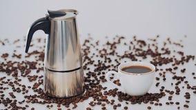 Кофеварка гейзера, кофейная чашка и кофейные зерна на белой предпосылке видеоматериал