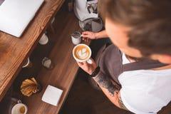 Кофеварка держа кружку с искусством latte Стоковая Фотография RF