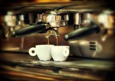 Кофеварка льет горячий кофе в 2 белых чашки Стоковое Фото
