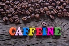 Кофеин слова и кофейные зерна стоковые изображения rf