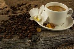Кофейная чашка и белая орхидея на деревянной предпосылке Стоковая Фотография RF