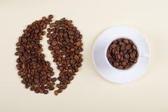 Кофейная чашка и большое кофейное зерно сделанные разбросанных фасолей стоковая фотография rf