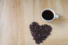 Кофейная чашка и в форме сердц кофейные зерна стоковое изображение