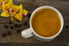Кофейная чашка и желтая орхидея на деревянной предпосылке Стоковые Изображения