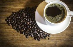Кофейная чашка и зажаренные в духовке кофейные зерна на деревянном стоковая фотография