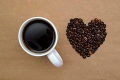Кофейная чашка и кофейные зерна в форме сердца, взгляд сверху Стоковое Изображение RF