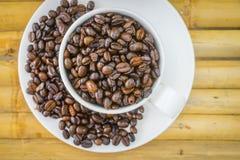 Кофейная чашка и кофейные зерна на бамбуковой предпосылке Стоковое фото RF