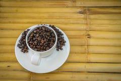 Кофейная чашка и кофейные зерна на бамбуковой предпосылке Стоковая Фотография