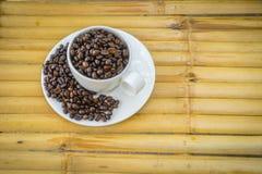 Кофейная чашка и кофейные зерна на бамбуковой предпосылке Стоковое Изображение