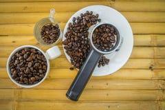 Кофейная чашка и кофейные зерна на бамбуковой предпосылке Стоковая Фотография RF