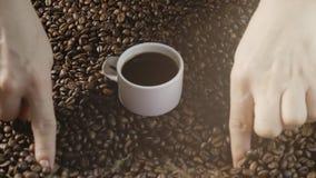 Кофейная чашка и кофейные зерна Руки ` s женщин рисуют сердце кофейных зерен Белая чашка испаряться кофе с зажаренный в духовке акции видеоматериалы