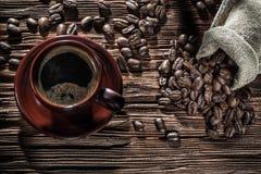 Кофейная чашка и мешок с фасолями на винтажной деревянной доске стоковые фото