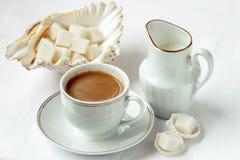 Кофейная чашка и поддонник с молоком и сахаром на белой предпосылке Стоковые Фотографии RF