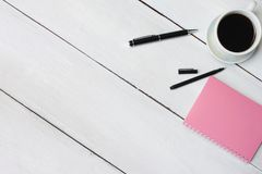 Кофейная чашка и ручка, тетрадь на белом деревянном столе и иметь экземпляр s стоковые изображения
