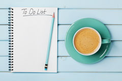 Кофейная чашка и тетрадь с для того чтобы сделать список на голубом деревенском столе сверху, планировать и идее проекта Стоковое фото RF