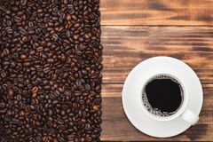 Кофейная чашка и фасоли на деревенской предпосылке Стоковое Изображение
