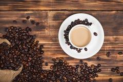 Кофейная чашка и фасоли на деревенской предпосылке Стоковая Фотография