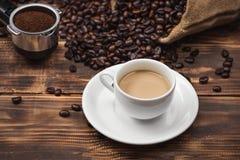 Кофейная чашка и фасоли на деревенской предпосылке Стоковая Фотография RF