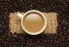 Кофейная чашка и фасоли на желтой предпосылке. Стоковая Фотография RF