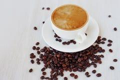 Кофейная чашка и фасоли, белая предпосылка натюрморт на одежде таблицы Стоковое фото RF