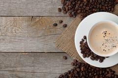 Кофейная чашка и фасоли на деревянном столе Стоковые Изображения RF