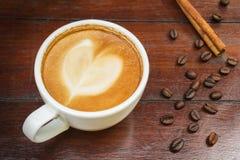 Кофейная чашка и фасоли на деревянном столе Стоковые Фотографии RF