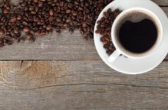 Кофейная чашка и фасоли на деревянном столе Стоковая Фотография