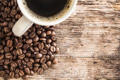 Кофейная чашка и фасоли на деревянном столе Стоковые Изображения