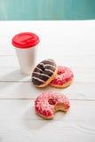 Кофейная чашка и 3 donuts с замороженностью шоколада и поленики donuts и концепция кофе Стоковые Изображения RF