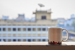 Кофейная чашка на балконе и запачканном взгляде buildingd запачкала взгляд buildingk в бамбуковом изоляте ручки на белизне Стоковые Изображения RF