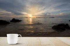 Кофейная чашка на верхней части деревянного стола на запачканной золотой предпосылке неба, моря и острова Стоковое Изображение