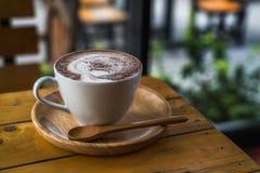 Кофейная чашка на деревянном столе с мягким светом стоковое фото rf