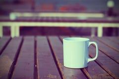 Кофейная чашка на деревянном (винтажная предпосылка) Стоковое Изображение RF