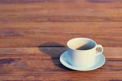 Кофейная чашка на деревянном (винтажная предпосылка) Стоковая Фотография RF